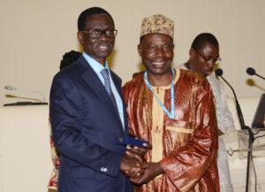 """Monsieur Soumaïla MOUMOUNI, recevant une distinction """"Grand Or"""", pour 30 années passées au service de la BOAD"""
